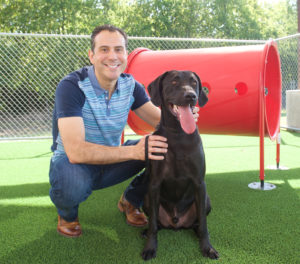 Rivera poses with Maverick, a Retriever, Labrador, Plott Hound mix.